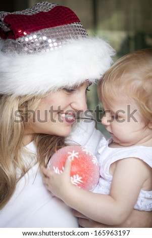 A smiling mum holding a cute toddler with a christmas decoration. Slight blur in photo - stock photo