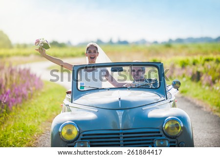 A smiling newlywed couple is driving a retro car on a country road for their honeymoon. - stock photo
