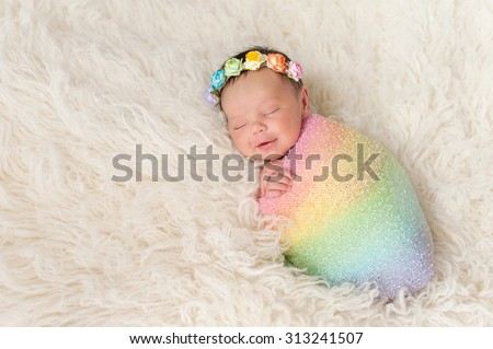 A smiling nine day old newborn baby girl bundled up in a rainbow colored swaddle. She is lying on a cream colored flokati (sheepskin) rug and wearing a crown made of roses. - stock photo
