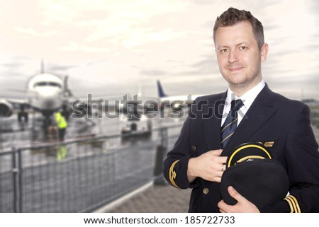 A smiling pilot in uniform on the tarmac - stock photo
