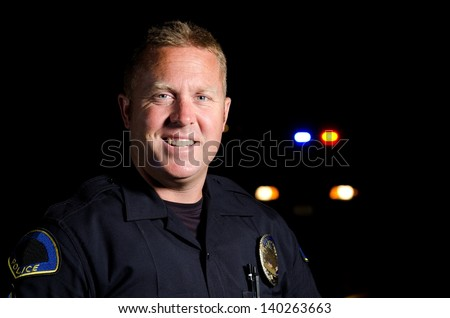 A smiling police officer at night with his patrol car in the background. - stock photo