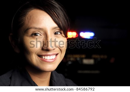 a smiling police officer with her patrol unit in the background with its lights on. - stock photo