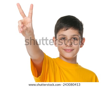 A smiling preteen boy shows victory sign against the white background - stock photo