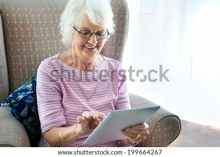 A smiling senior woman sitting in her couch holding a touchscreen - stock photo