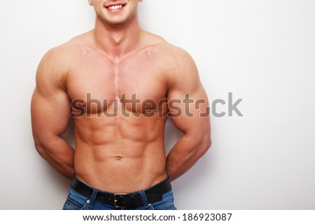 A smiling shirtless man in jeans - stock photo