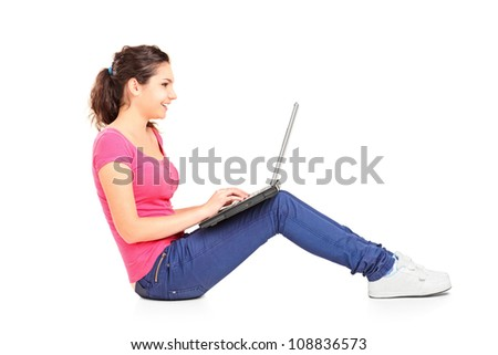 A smiling teenager doing her homework on a laptop isolated on white background - stock photo
