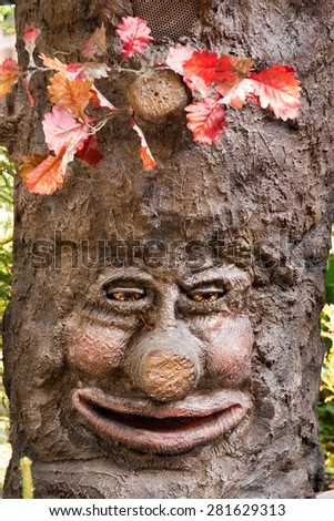 a smiling tree with a laughing face - stock photo