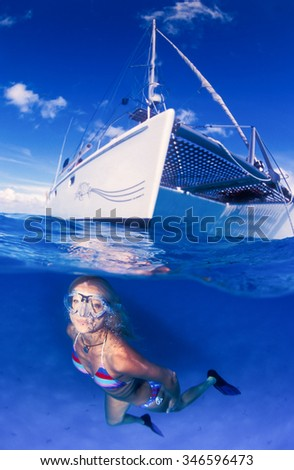 A smiling underwater model in a brightly colored bikini swimming towards the camera in very clear and very blue water - stock photo