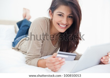 A smiling woman holding her credit card and tablet in her hands as she looks in front of her. - stock photo