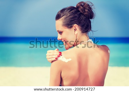 A smiling woman is applying sunblock on the beach, vintage-style photo. - stock photo