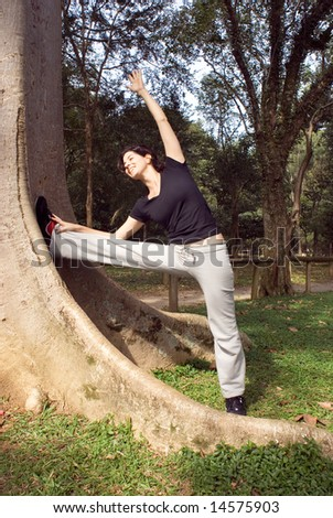 A smiling woman is standing next to a tree.  She is looking at the tree and stretching.  Vertically framed photo. - stock photo