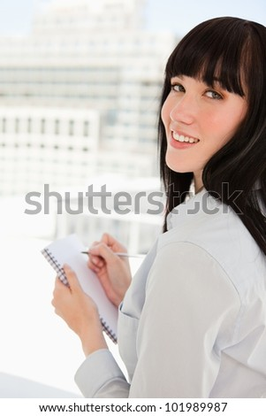 A smiling woman looking at the camera with a notepad in her hand - stock photo