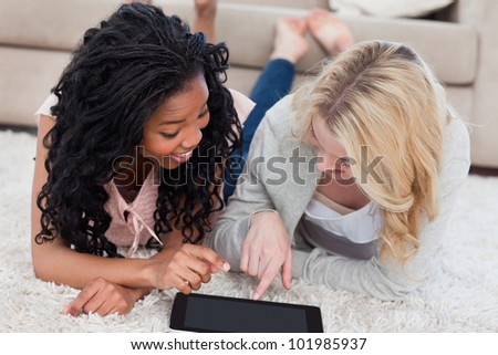 A smiling woman lying next to her smiling friend is pointing at a tablet - stock photo