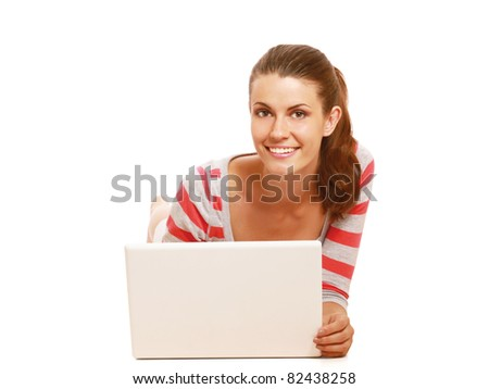 A smiling woman lying on the floor with a laptop, isolated on white - stock photo