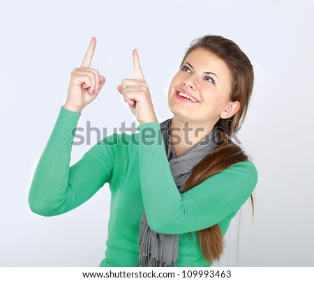 A smiling woman pointing and looking up, isolated on white - stock photo