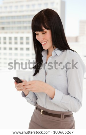 A smiling woman sending a text message from her mobile while at work - stock photo