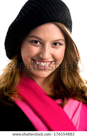 A smiling woman wearing a black hat and a pink scarf. - stock photo