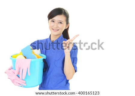 A smiling woman with a bucket - stock photo