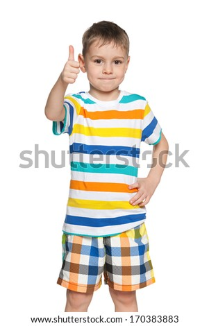 A smiling young boy in a striped shirt holds his thumb - stock photo