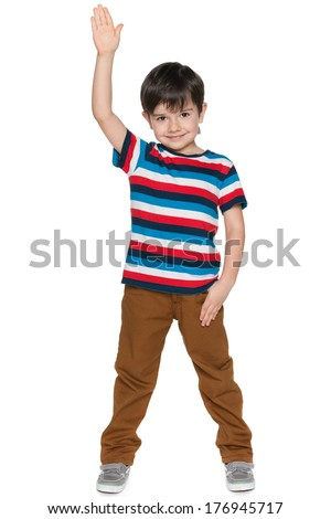 A smiling young boy stretching his right hand up on the white background - stock photo
