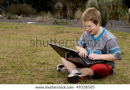 A smiling young boy using a laptop computer - stock photo