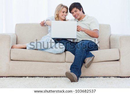 A smiling young couple are sitting down on a couch looking at a laptop - stock photo