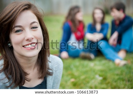 A smiling young girl with three friends in the background - stock photo