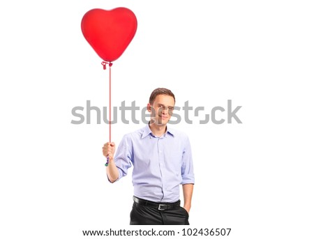 A smiling young male holding a red heart shaped balloon isolated on white background - stock photo