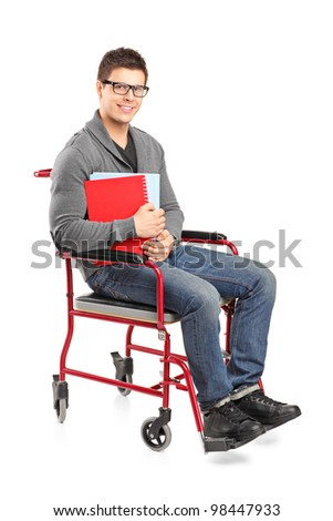 A smiling young male in a wheelchair holding notebooks isolated on white background - stock photo