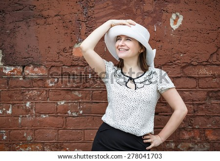 A smiling young woman in a white blouse and a hat posing against the backdrop of an old vintage brown brick wall. Female hand holds a hat. Photos in retro style. - stock photo