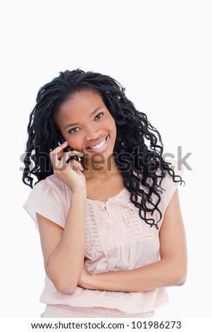 A smiling young woman looking at the camera is talking on her mobile phone - stock photo