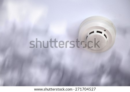 A smoke detector installed at a ceiling with smoke - stock photo