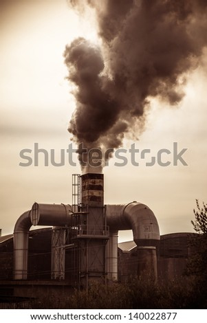 a smokestack erupting toxic fumes in the atmosphere - stock photo
