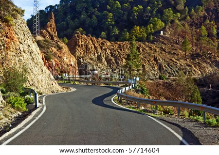 A smooth paved road winding through mountains - stock photo