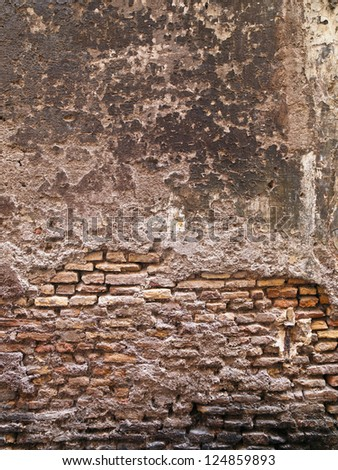 A smoothed over wall is worn away to expose the brick underneath - stock photo