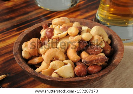 A snack bowl of mixed nuts on a bar counter with beer - stock photo