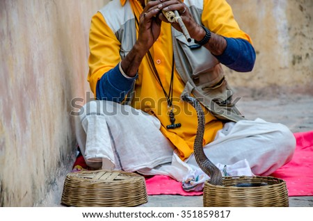 a snake man showing a pet snake in Amber fort to visitors. this is how he earns bread and butter - stock photo