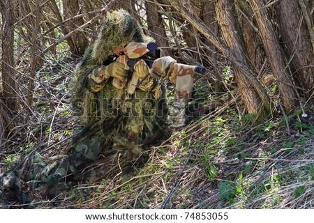 a sniper hiding in the bushes - stock photo