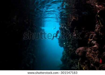 A snorkeler explores a dark grotto in the Solomon Islands. Coral reefs in this Melanesian region are exceedingly diverse in terms of habitats. The area also offers great scuba diving and snorkeling. - stock photo