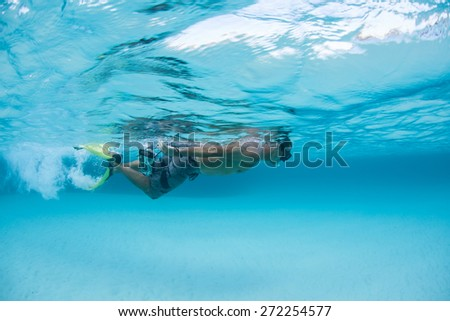 A snorkeler swims through a clear lagoon in Raja Ampat, Indonesia. This region is in the heart of the Coral Triangle, harbors high marine biodiversity and offers world class diving and snorkeling. - stock photo