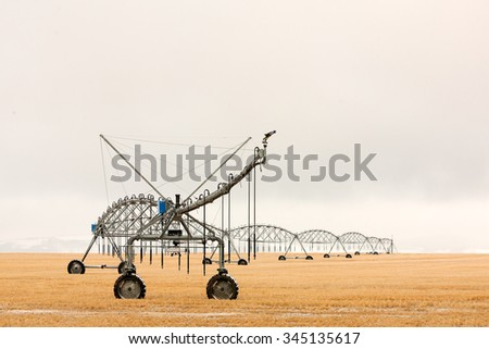 A snow covered center pivot irrigation unit sits alone in a field during winter waiting to be used again in the spring. - stock photo