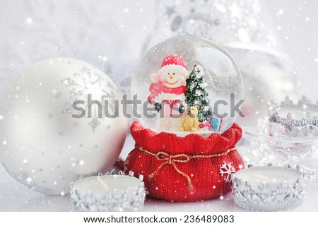 A snow globe with snowman and Christmas decorations - stock photo