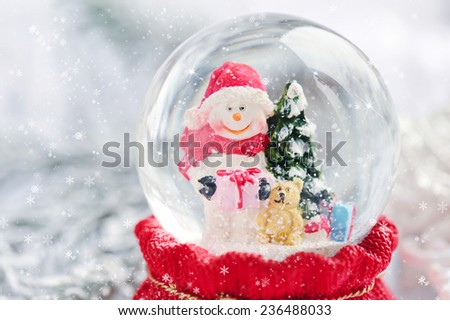 A snow globe with snowman on festive background - stock photo