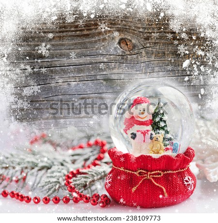 A snow globe with snowman on the snow-covered wooden background - stock photo