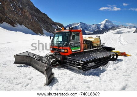 A snow groomer in the swiss alps - stock photo