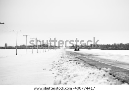 A snow plow clearing a snow laden highway in a black and white rural winter landscape - stock photo