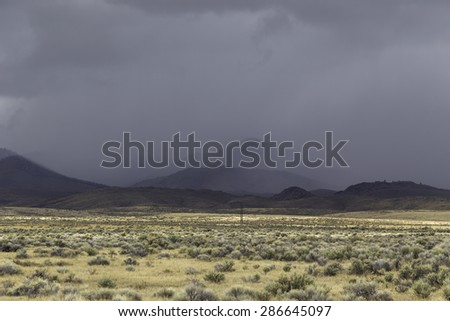 A snow storm flowing over the Rockies and into the desert terrain in northern Wyoming. - stock photo