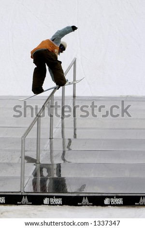 A snowboarder doing a hand rail. - stock photo