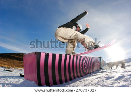 A snowboarder executes a radical backside slide on a rail in a snow park. - stock photo