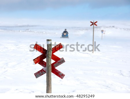 A snowmobile behind a red wooden signpost on a winter day in northern Sweden - stock photo
